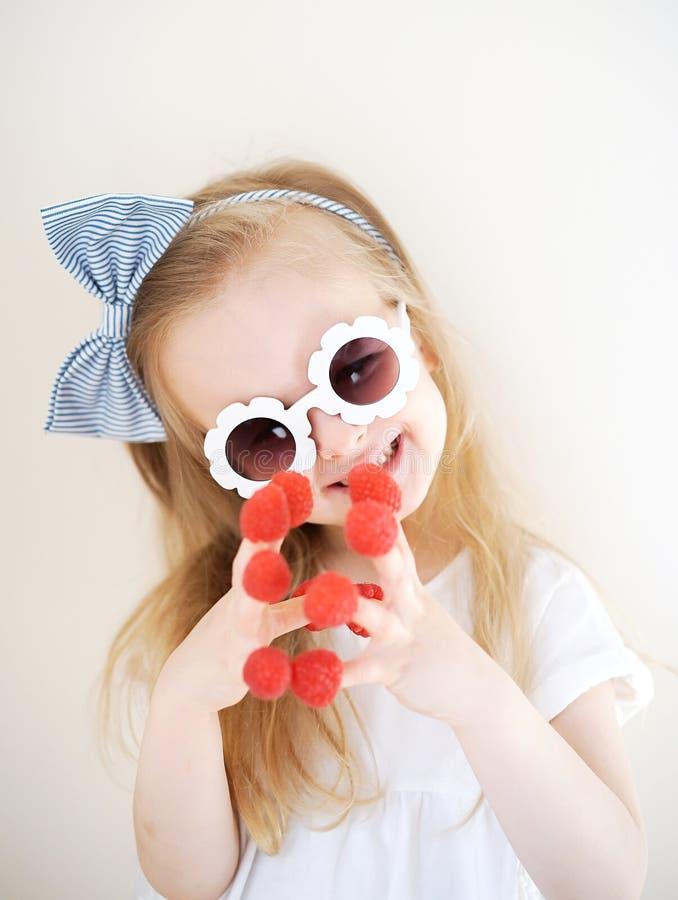 Λίγο χαριτωμένο ξανθό κορίτσι με τα σμέουρα στα δάχτυλά της, διαφορετικές συγκινήσεις, εσωτερικές στοκ εικόνες