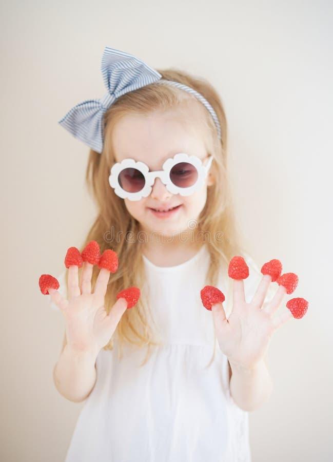 Λίγο χαριτωμένο ξανθό κορίτσι με τα σμέουρα στα δάχτυλά της, διαφορετικές συγκινήσεις, εσωτερικές στοκ φωτογραφία