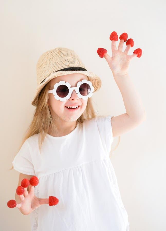 Λίγο χαριτωμένο ξανθό κορίτσι με τα σμέουρα στα δάχτυλά της, διαφορετικές συγκινήσεις, εσωτερικές στοκ φωτογραφία με δικαίωμα ελεύθερης χρήσης