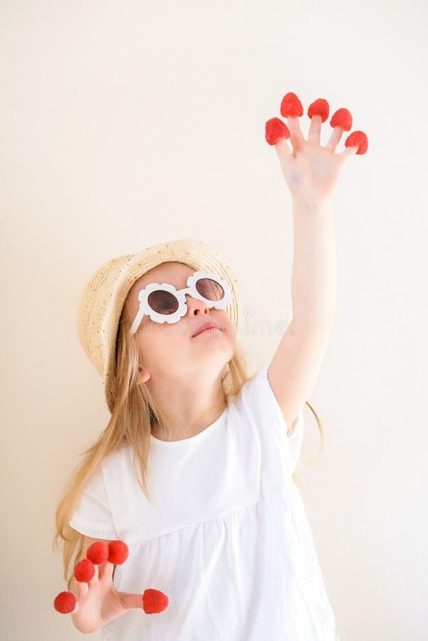 Λίγο χαριτωμένο ξανθό κορίτσι με τα σμέουρα στα δάχτυλά της, διαφορετικές συγκινήσεις, εσωτερικές στοκ φωτογραφίες με δικαίωμα ελεύθερης χρήσης