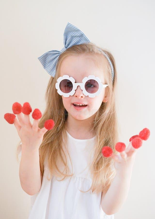 Λίγο χαριτωμένο ξανθό κορίτσι με τα σμέουρα στα δάχτυλά της, διαφορετικές συγκινήσεις, εσωτερικές στοκ εικόνα