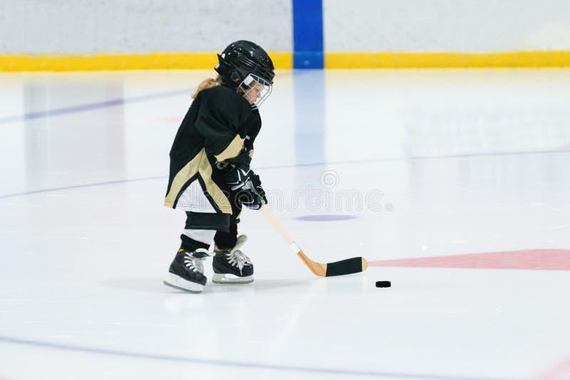 Λίγο χαριτωμένο ξανθό κορίτσι παίζει το χόκεϋ στον πλήρη εξοπλισμό στο στάδιο στοκ φωτογραφία