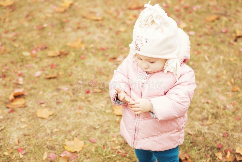 Λίγο χαριτωμένο παιδί κοριτσιών που έχει τη διασκέδαση στο πάρκο στα θερμά ενδύματα & x28 φθινοπώρου  στοκ εικόνα