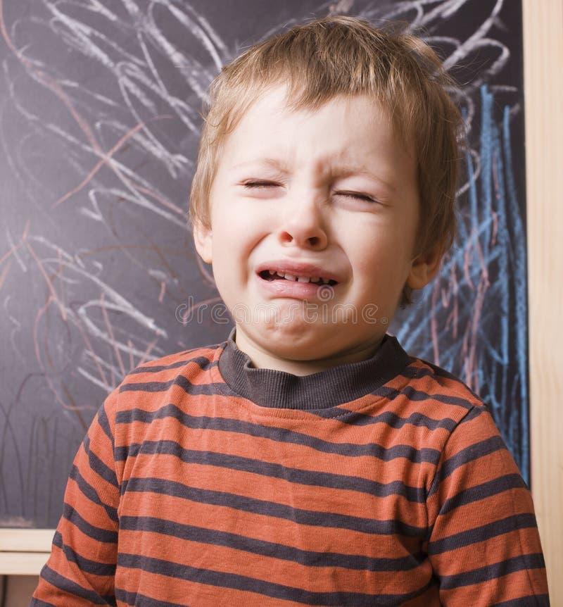 Λίγο χαριτωμένο πραγματικό αγόρι που κραυγάζει και που φωνάζει στο σχολείο κοντά στον πίνακα κοντά επάνω στοκ εικόνες με δικαίωμα ελεύθερης χρήσης