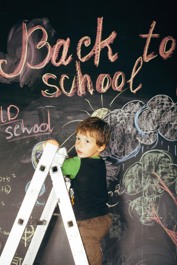 Λίγο χαριτωμένο πραγματικό αγόρι στον πίνακα στην τάξη στοκ φωτογραφία με δικαίωμα ελεύθερης χρήσης