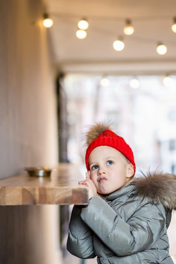 Λίγο χαριτωμένο σκεπτικό καυκάσιο κορίτσι στο κόκκινο πλεκτό καπέλο και θερμή συνεδρίαση σακακιών στο μετρητή υπαίθρια και σκεπτό στοκ εικόνα με δικαίωμα ελεύθερης χρήσης