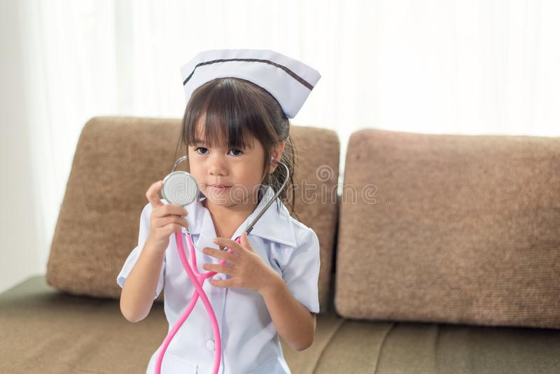 Λίγο χαριτωμένο χαμογελώντας ασιατικό κορίτσι που φορά μια νοσοκόμα ομοιόμορφη με το στηθοσκόπιο στοκ εικόνες