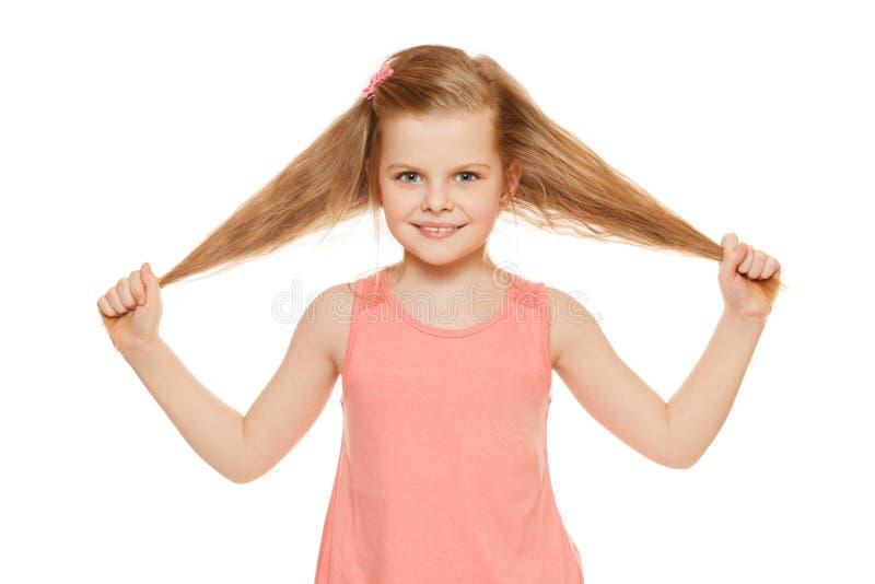 Λίγο χαρούμενο κορίτσι διασκέδασης σε ένα ρόδινο πουκάμισο κρατά την τρίχα χεριών, που απομονώνεται στο άσπρο υπόβαθρο στοκ εικόνα