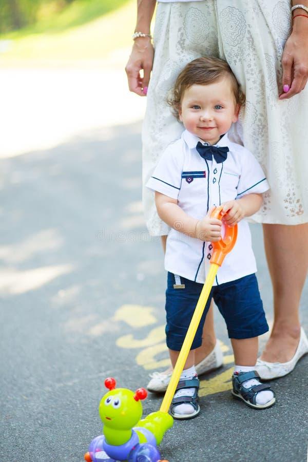 Λίγο όμορφο αγόρι που κρύβει στα πόδια της μητέρας στοκ εικόνα με δικαίωμα ελεύθερης χρήσης