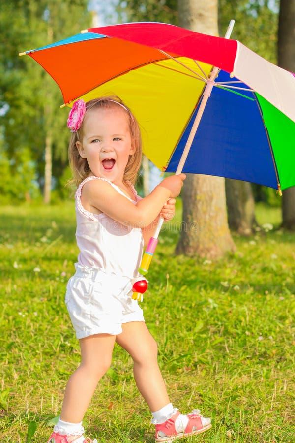 Λίγο όμορφο κορίτσι διασκέδασης περπατά στο πάρκο με τη ζωηρόχρωμη ομπρέλα στοκ εικόνες