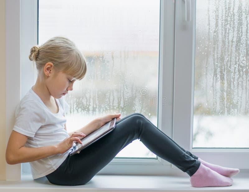 Λίγο όμορφο κορίτσι με μια ταμπλέτα στο παράθυρο στοκ φωτογραφία