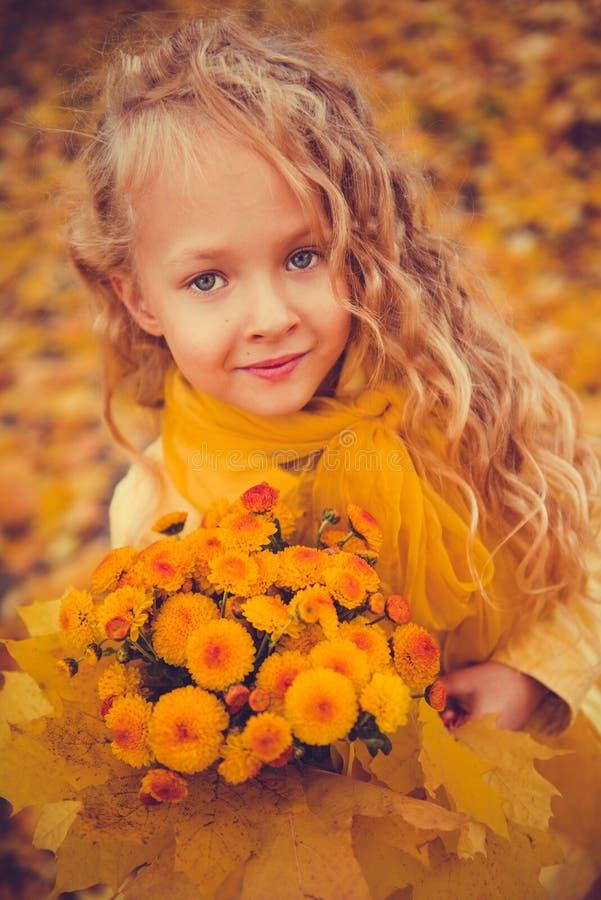 Λίγο όμορφο κορίτσι με τα ξανθά μαλλιά στο υπόβαθρο φθινοπώρου στοκ φωτογραφίες