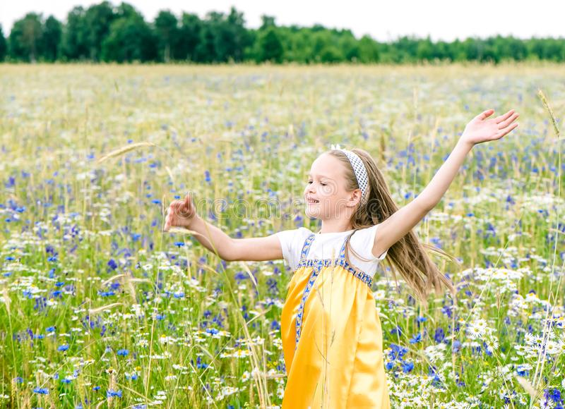 Λίγο όμορφο κορίτσι στην κίτρινη ρωσική επιλογή φορεμάτων ανθίζει στον τομέα των άγριων λουλουδιών τη θερινή ημέρα στοκ φωτογραφία