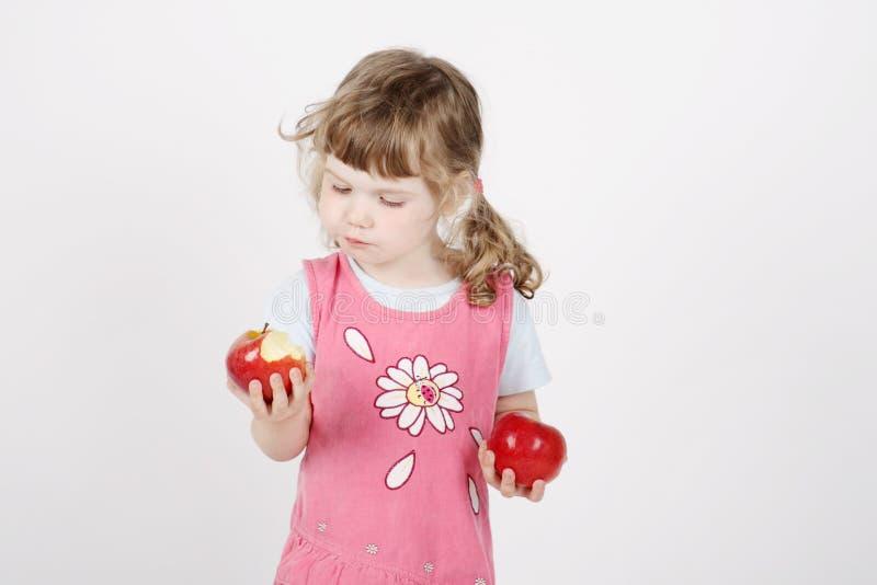 Λίγο όμορφο κορίτσι στο ροζ τρώει το μήλο στοκ φωτογραφία