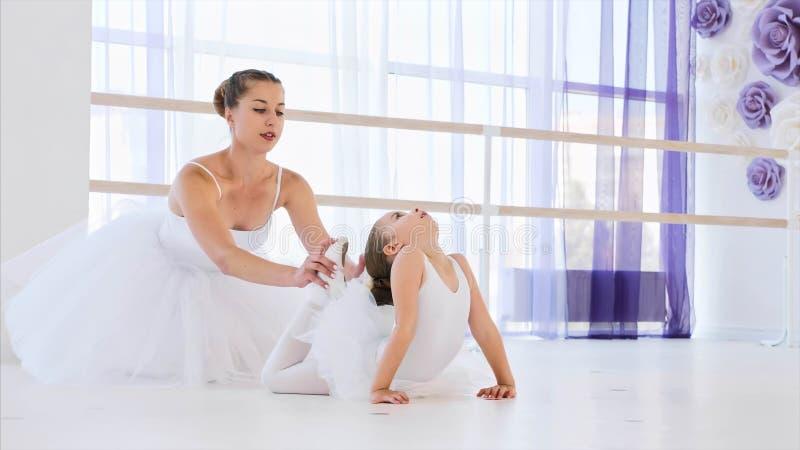 Λίγο ballerina στο άσπρο tutu τεντώνει στο βάτραχο θέτει με το δάσκαλο μπαλέτου στοκ εικόνες με δικαίωμα ελεύθερης χρήσης