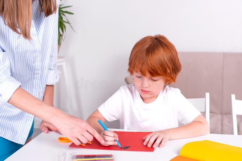 Λίγο redhead αγόρι με μια παραμάνα ή μια μητέρα ή ο δάσκαλος κάθεται στον πίνακα και το χρώμα με τα χρώματα στοκ εικόνες