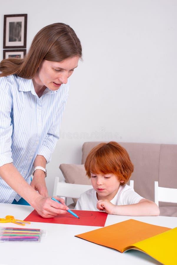 Λίγο redhead αγόρι με μια παραμάνα ή μια μητέρα ή ο δάσκαλος κάθεται στον πίνακα και το χρώμα με τα χρώματα στοκ φωτογραφίες