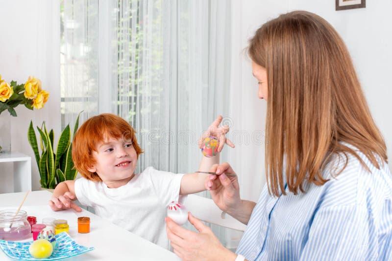 Λίγο redhead αγόρι με μια παραμάνα ή μια μητέρα ή ο δάσκαλος κάθεται στον πίνακα και το χρώμα με τα χρώματα στοκ φωτογραφία με δικαίωμα ελεύθερης χρήσης