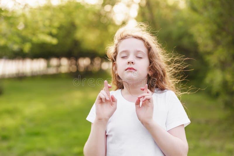 Λίγο redhead κορίτσι κάνει την επιθυμητή επιθυμία υπαίθρια στοκ εικόνες