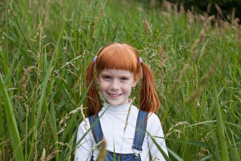 Λίγο redhead κορίτσι με τα λαμπιρίζοντας μάτια και τις φακίδες στοκ φωτογραφίες