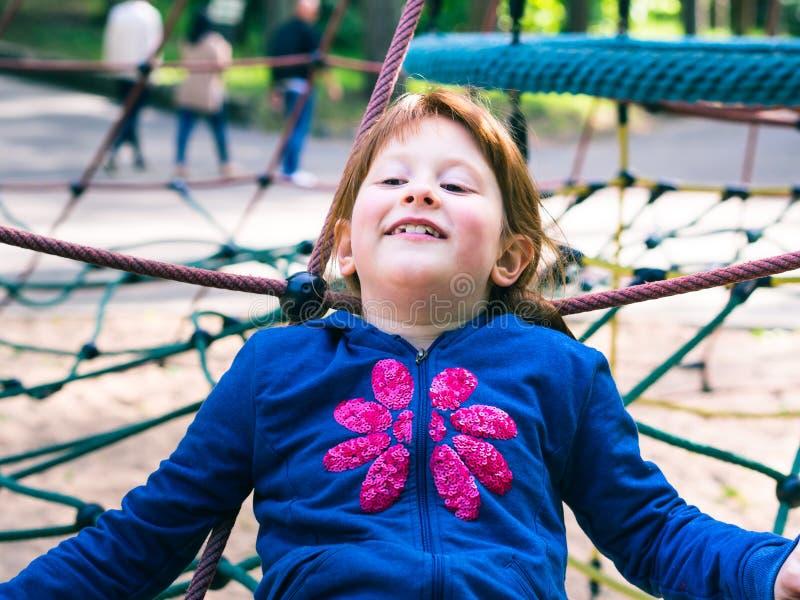 Λίγο redhead κορίτσι που παίζει στην παιδική χαρά στοκ φωτογραφία με δικαίωμα ελεύθερης χρήσης