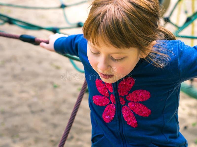 Λίγο redhead κορίτσι που παίζει στην παιδική χαρά στοκ εικόνα