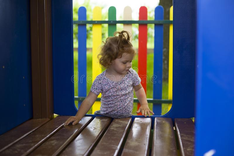Λίγο redhead κορίτσι προσπαθεί να αναρριχηθεί σε ένα ξύλινο σπίτι στην παιδική χαρά στοκ εικόνες