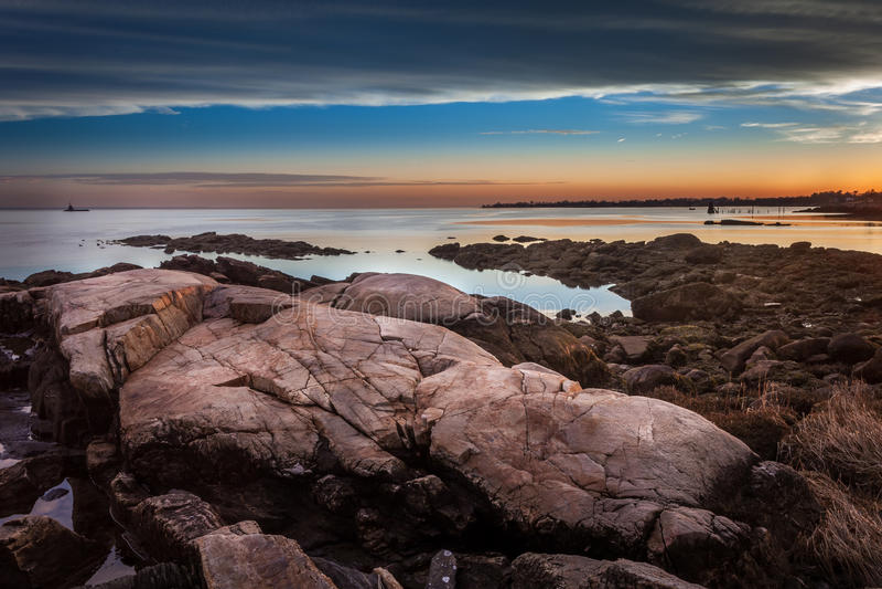 Λίθοι στην ακτή στο ηλιοβασίλεμα με το φάρο στην απόσταση στοκ φωτογραφίες