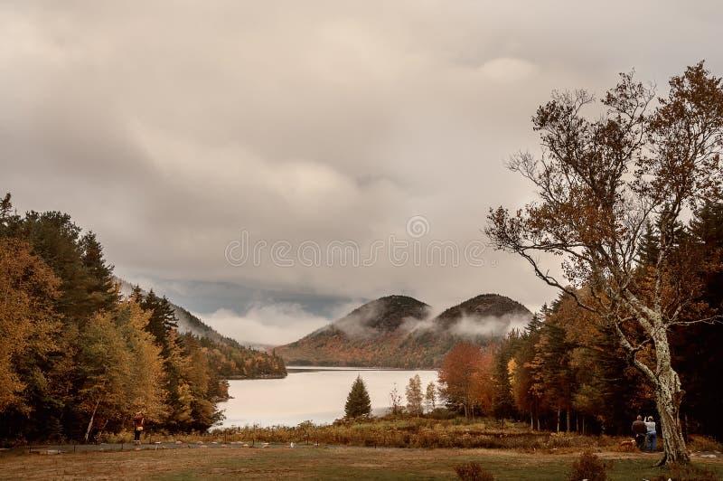 Λίμνη και βουνά στα ζωηρόχρωμα δέντρα φθινοπώρου τουρίστες που φωτογραφίζουν το τοπίο στοκ φωτογραφία