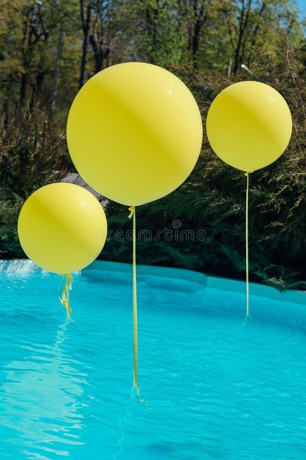 Λίμνη με τα μεγάλα κίτρινα μπαλόνια υπαίθρια Κόμμα Poolside Τα μπαλόνια στο νερό Διακοσμήσεις για τη γαμήλια τελετή στοκ εικόνες