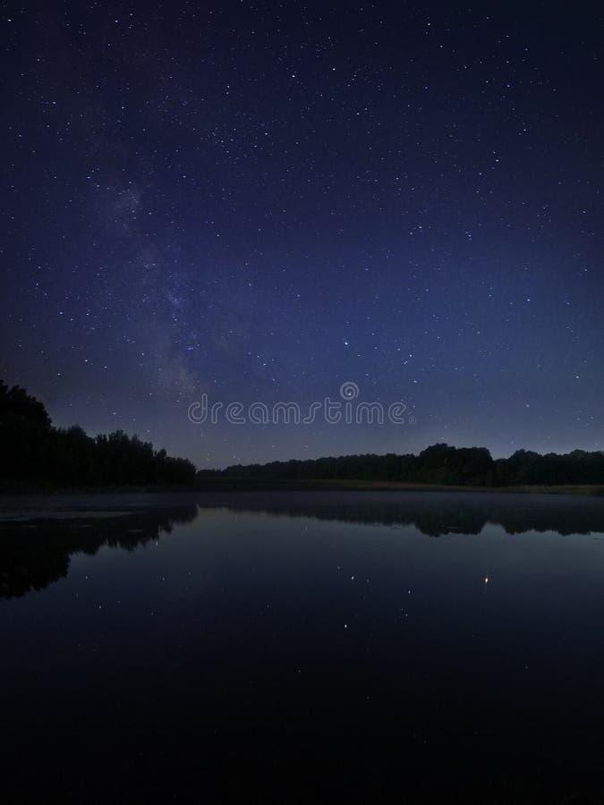 Λίμνη νύχτας κάτω από τα γαλακτώδη αστέρια τρόπων στοκ εικόνες