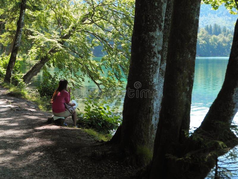 Λίμνη Alpsee βουνών στη Γερμανία με να ονειρευτεί τη συνεδρίαση κοριτσιών στην ακτή στοκ εικόνα