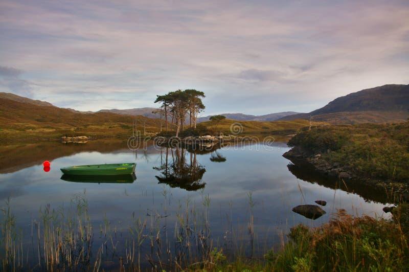 Λίμνη Assynt στο ηλιοβασίλεμα με τη βάρκα, δέντρα, βουνά, αντανακλάσεις στο νερό στοκ εικόνα με δικαίωμα ελεύθερης χρήσης