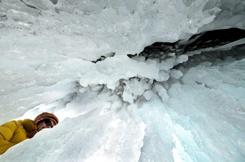 Λίμνη Baikal, Ρωσίας - 10 Μαρτίου, 2018: Η νέα γυναίκα κρυφοκοιτάζει grot πάγου με τους σταλακτίτες και stalagnite στοκ εικόνες με δικαίωμα ελεύθερης χρήσης