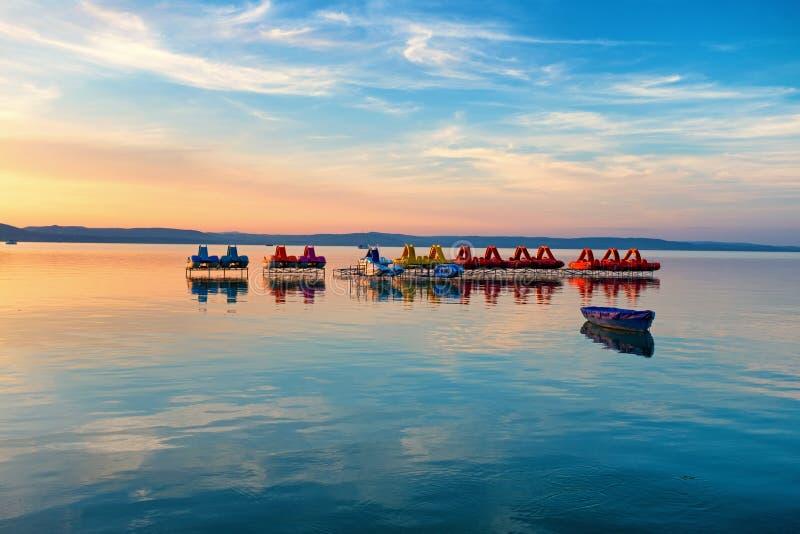 Λίμνη Balaton στο ηλιοβασίλεμα με τα pedalos, τα καγιάκ και μια βάρκα στο πρώτο πλάνο στοκ εικόνες με δικαίωμα ελεύθερης χρήσης
