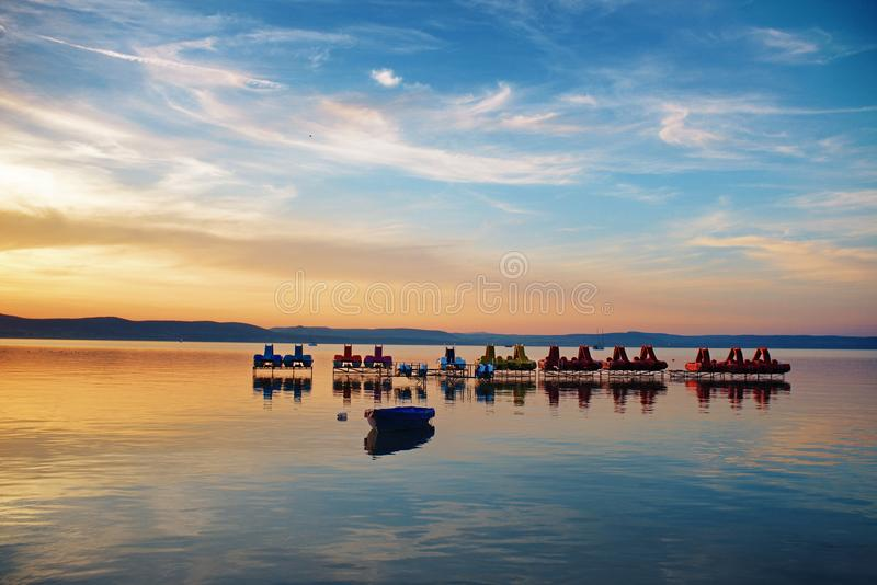 Λίμνη Balaton στο ηλιοβασίλεμα με τα pedalos και βάρκες πενταλιών σε Balaontlelle, Ουγγαρία στοκ φωτογραφία με δικαίωμα ελεύθερης χρήσης