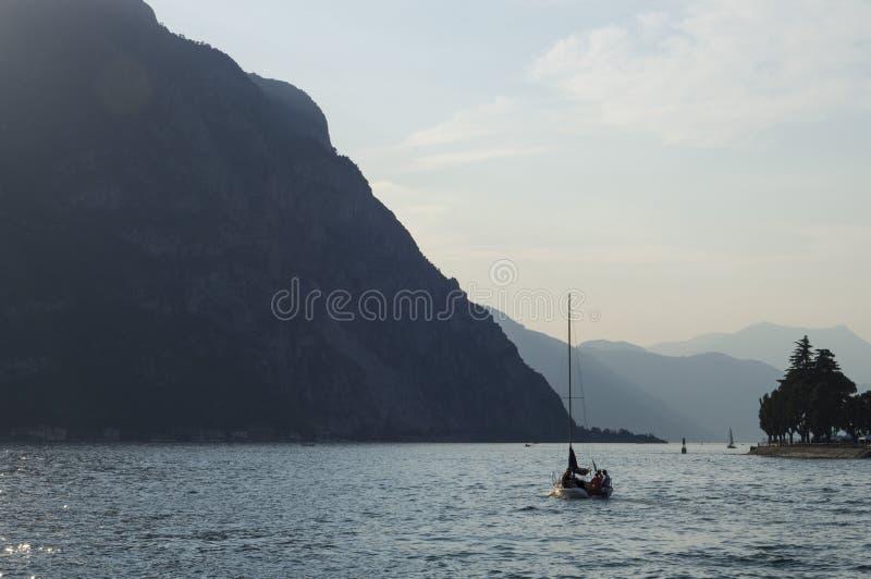 Λίμνη Como στην ιταλική πόλη Lecco που περιβάλλεται από τα βουνά Ένα πλέοντας γιοτ Ηλιοφάνεια βραδιού στοκ φωτογραφία