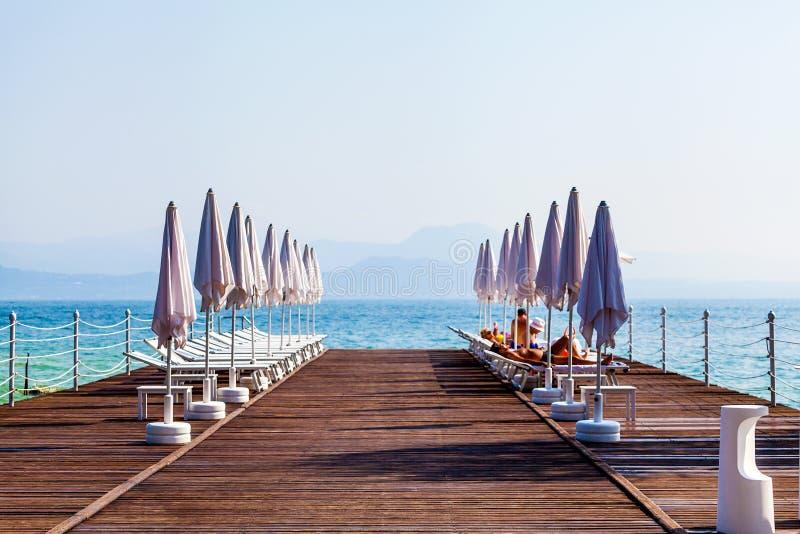 Λίμνη Garda τοπίων με την αποβάθρα, τις καρέκλες παραλιών και τις ομπρέλες στο πρώτο πλάνο, Ιταλία στοκ εικόνες