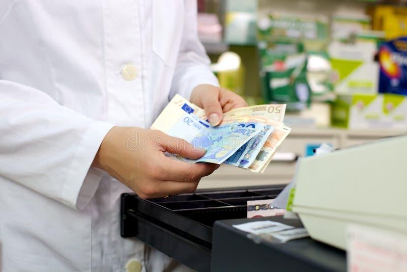 Λαβή ευρώ χρημάτων από το φαρμακοποιό στο μετρητή στοκ εικόνες με δικαίωμα ελεύθερης χρήσης