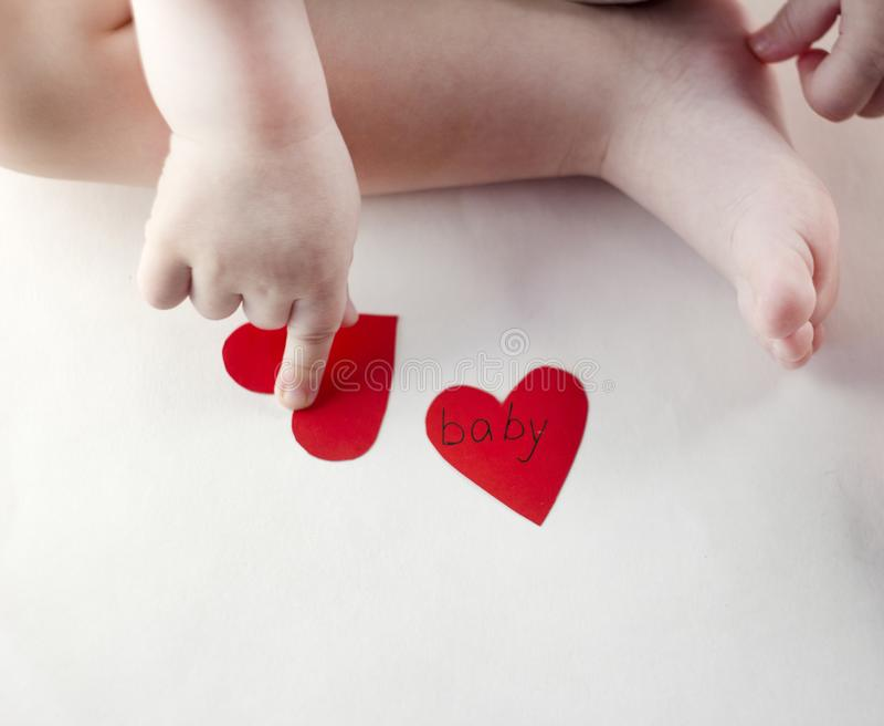 Λαβή και ένα πόδι μωρών ` s και μια κόκκινη καρδιά μικρά στοκ εικόνες