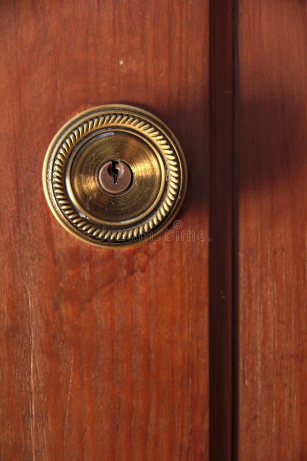 Λαβή πορτών χαλκού σε μια ξύλινη πόρτα στοκ εικόνα
