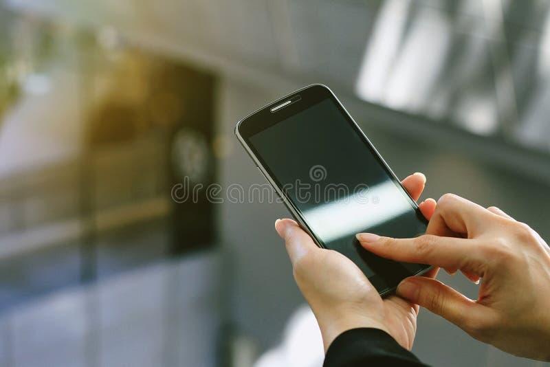 Λαβή χεριών κινηματογραφήσεων σε πρώτο πλάνο χρησιμοποιώντας το κινητό τηλέφωνο ή διαβάζοντας τις ειδήσεις από το smartphone στοκ εικόνα με δικαίωμα ελεύθερης χρήσης