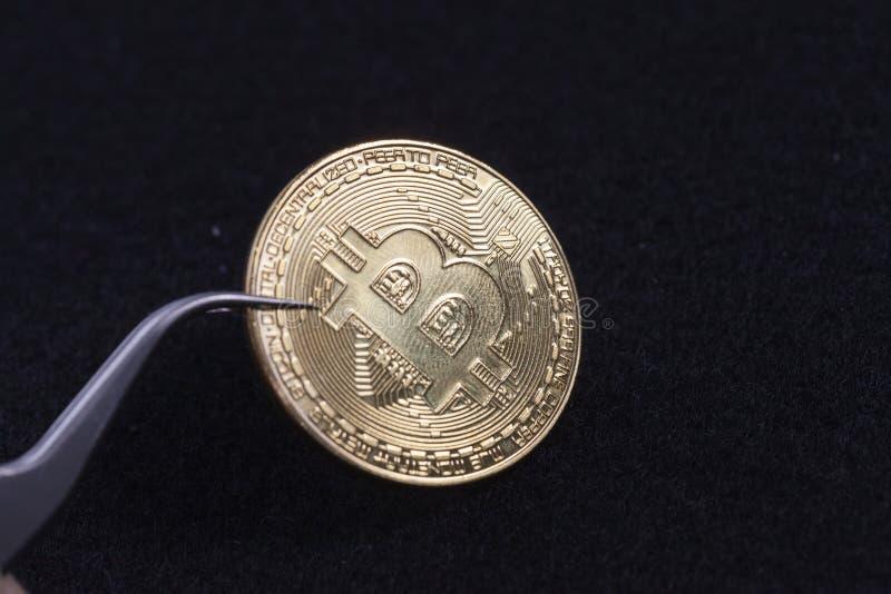 Λαβίδες και bitcoin στο μαύρο υπόβαθρο στοκ εικόνες