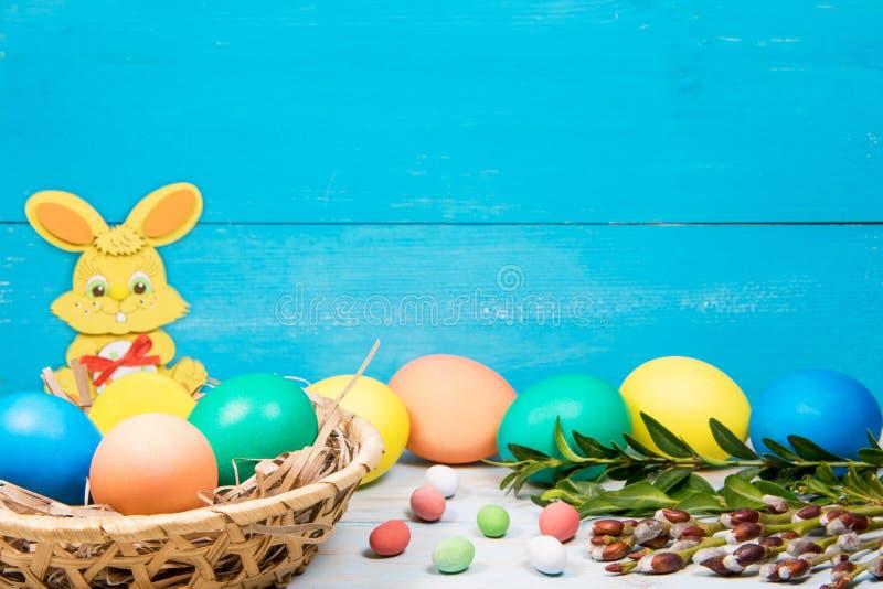 Λαγουδάκι και αυγά Πάσχας σε ένα καλάθι, που χρωματίζεται στο διαφορετικό χρώμα σε ένα μπλε υπόβαθρο με μια θέση για την επιγραφή στοκ φωτογραφίες με δικαίωμα ελεύθερης χρήσης