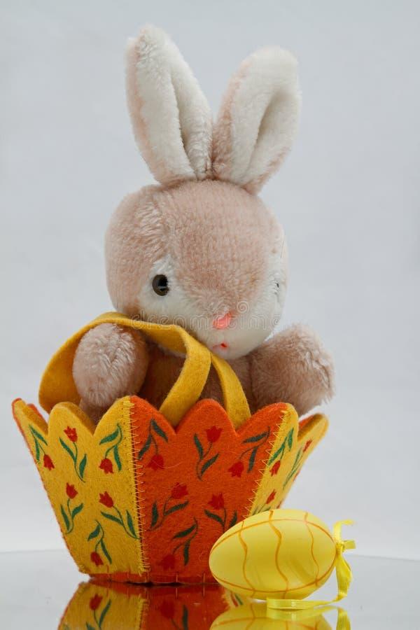 Λαγουδάκι με ένα καλάθι Πάσχας και ένα κίτρινο αυγό Πάσχας στοκ φωτογραφίες με δικαίωμα ελεύθερης χρήσης