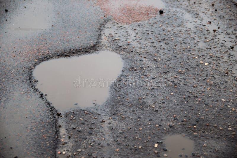 Λακκούβα στο πεζοδρόμιο Κακή άσφαλτος Σπασμένος δρόμος στοκ εικόνες με δικαίωμα ελεύθερης χρήσης