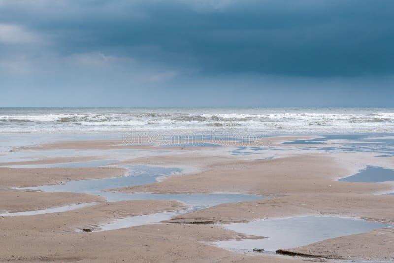 Λακκούβες σε μια παραλία at low tide με τα χαμηλά βαριά γκρίζα σύννεφα στοκ φωτογραφία