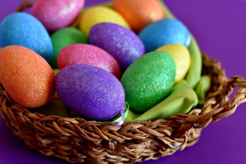Λαμπιρίζοντας ακτινοβολώντας χρωματισμένα αυγά Πάσχας καραμελών σε ένα ψάθινο καλάθι στοκ εικόνες με δικαίωμα ελεύθερης χρήσης