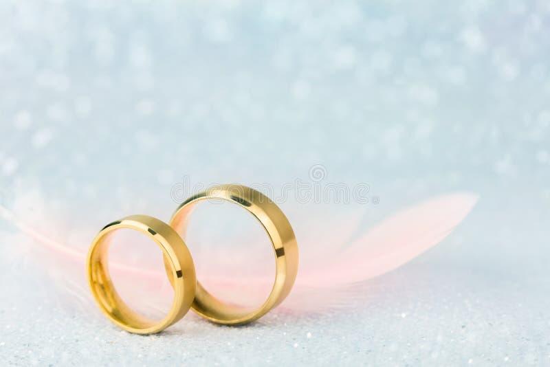 Λαμπιρίζοντας γαμήλια κάρτα - δύο γαμήλια δαχτυλίδια και ελαφρύς άγγελος Feath στοκ φωτογραφίες