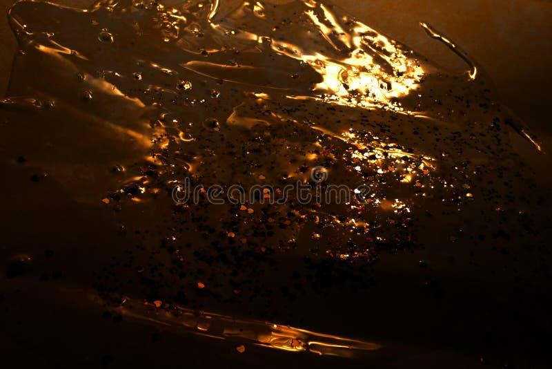 Λαμπρά χρυσά μόρια σχεδίων στο σκοτεινό υγρό πυροβολισμό στούντιο κινηματογραφήσεων σε πρώτο πλάνο υποβάθρου στοκ φωτογραφίες με δικαίωμα ελεύθερης χρήσης